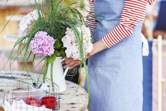 Woman decorating the table with flowers — Stock Photo