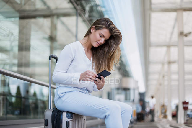 Young businesswoman sitting outdoors on luggage using cell phone — Stock Photo