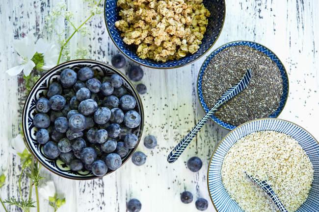 Tazones de granola, arándanos, semillas de chía negra y amaranto - foto de stock
