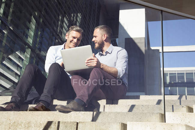 Two smiling businessmen sitting on stairs and using laptop — Stock Photo