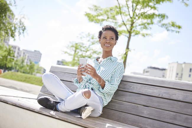Ritratto di giovane donna sorridente con cellulare e auricolari seduta sulla panchina — Foto stock