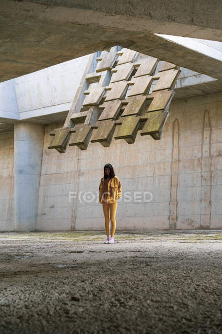 Young woman wearing yellow jeans clothes, standing in concrete building — Stock Photo