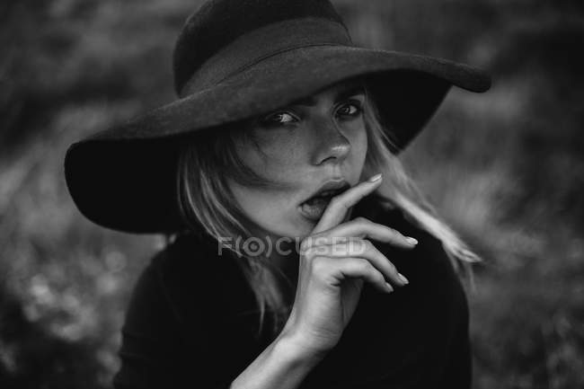 Portrait of young woman wearing black hat and posing on camera, keeping fingers at lips — Stock Photo