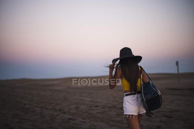 Назад погляд дівчинка-підлітка в капелюсі з плеча сумку ходьба на пляжі на заході сонця — стокове фото