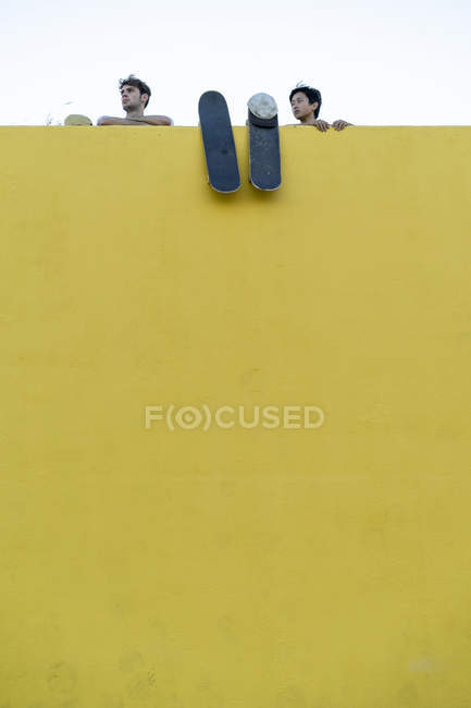 Два молодых человека со скейтбордами за высокой желтой стеной оглядываются вокруг — стоковое фото