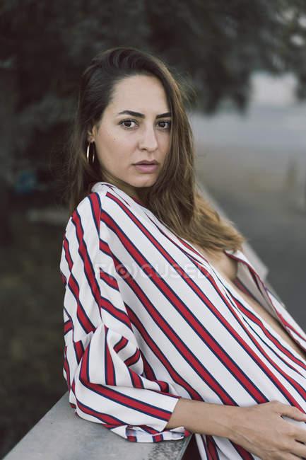 Портрет жінки носіння розстебнутій смугастої сорочки — стокове фото