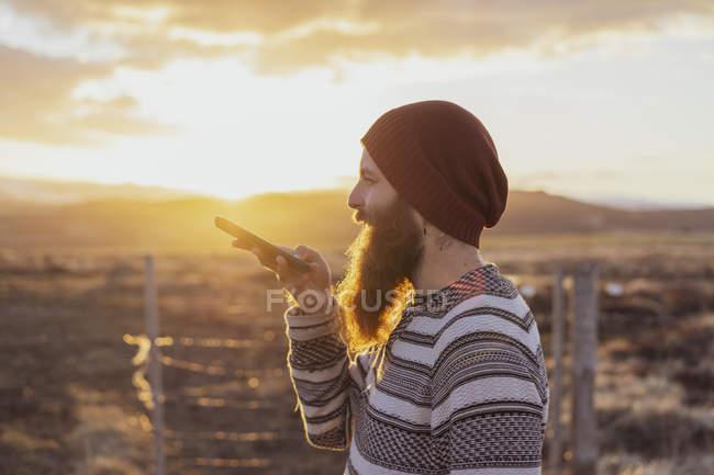 Исландия, молодой человек с помощью смартфона, голосовое сообщение — стоковое фото
