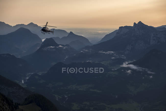 Austria, Salzburg State, Loferer Steinberge, helicopter in mountainscape at twilight — стокове фото