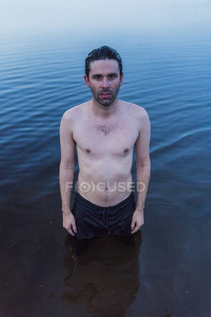 Man with bare chest standing in lake — Stock Photo