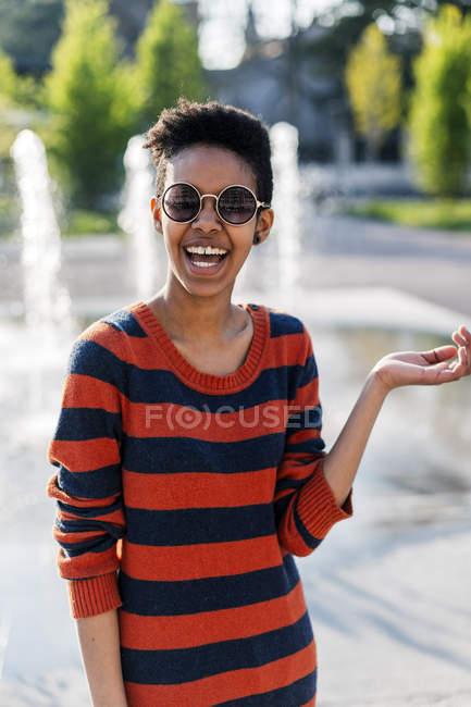 Портрет сміху молода жінка в сонцезахисні окуляри і смугастий пуловер — стокове фото