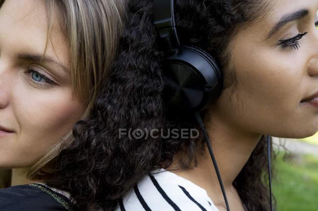 Две подруги в парке слушают музыку — стоковое фото