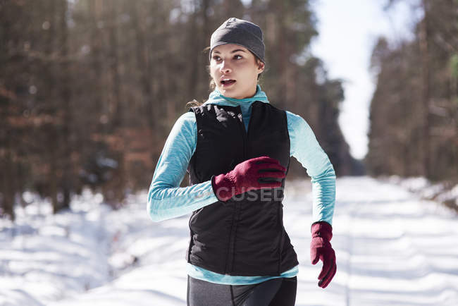 Portrait of young woman jogging in winter forest — Stock Photo