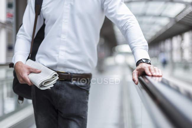 Nahaufnahme eines Geschäftsmannes auf fahrendem Gehweg mit Zeitung — Stockfoto