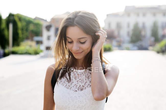 Retrato de uma jovem sorridente na cidade olhando para baixo — Fotografia de Stock