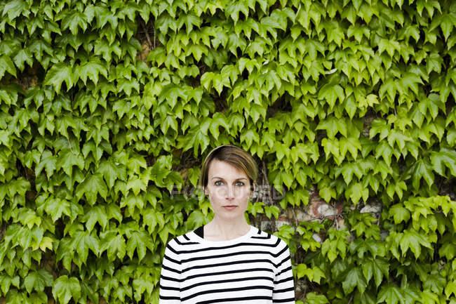 Portrait de femme sérieuse posant devant la verdure de la façade — Photo de stock