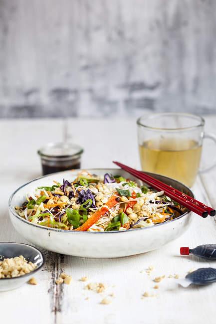 Salat mit Glasnudeln, Kohl, Karotten, Paprika, Frühlingszwiebeln, Erdnüssen und scharfem Thai-Dressing — Stockfoto