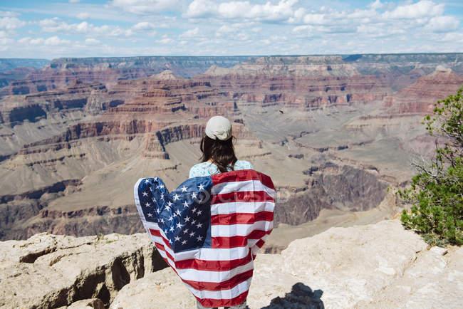 Usa, Arizona, femme souriante arborant le drapeau américain au parc national du Grand Canyon, vue de l'arrière — Photo de stock