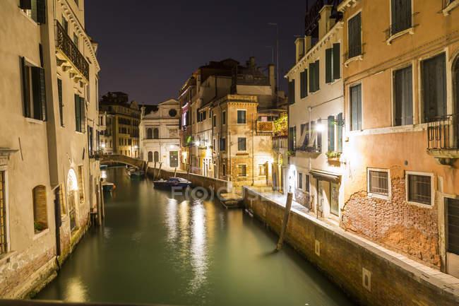 Italia, Venecia, Canal y casas por la noche - foto de stock