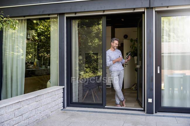 Sorridente maturo in piedi alla porta francese a casa con un tablet — Foto stock