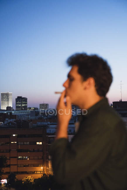 Jovem fumando charro no telhado na cidade da noite — Fotografia de Stock