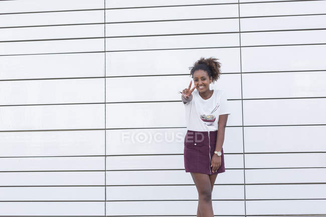 Portrait of smiling young african american student girl gesturing peace sign with fingers on camera — Stock Photo