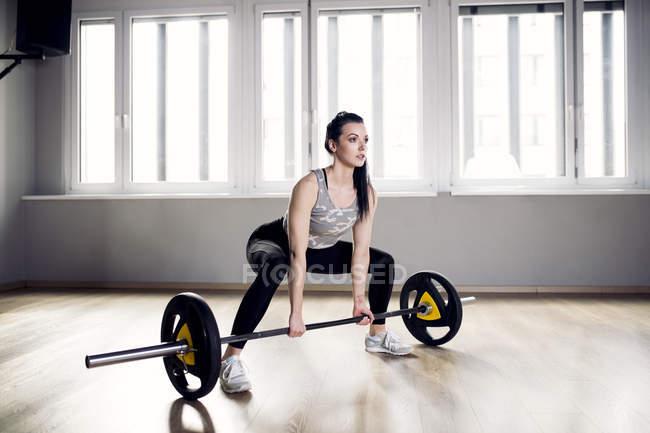 Женщина готовится к тяжелой атлетике в спортзале — стоковое фото