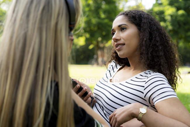Дві дівчини в парку слухають музику, використовуючи смартфон. — Stock Photo