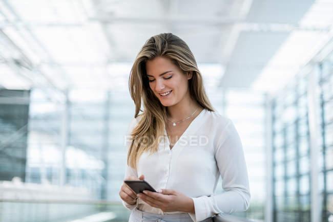 Улыбающаяся молодая женщина, стоящая у ограждения с помощью мобильного телефона — стоковое фото