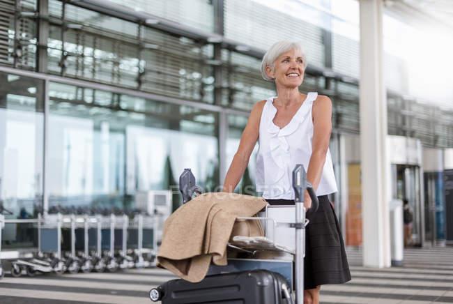 Smiling senior woman pushing baggage cart at airport — Stock Photo