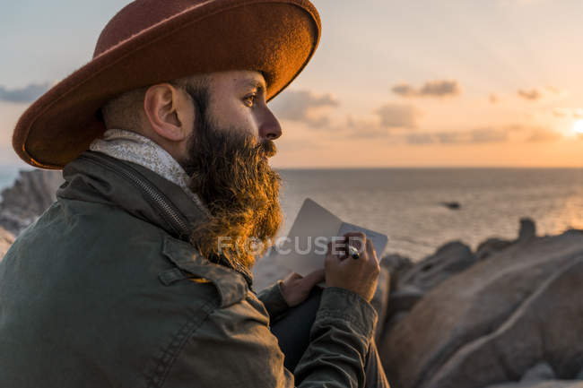 Italy, Sardinia, bearded man with notebook in front of the sea at sunset — Stock Photo