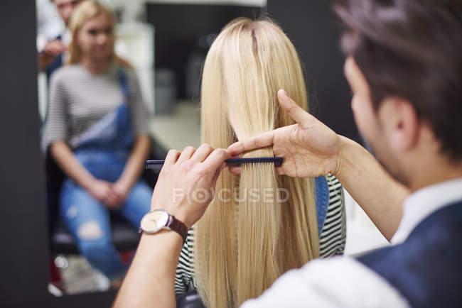 Vista posteriore del parrucchiere pettinando i capelli della donna — Foto stock
