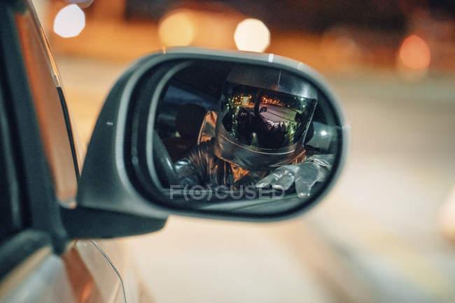 Reflejo del hombre del espacio en el espejo del ala del coche por la noche - foto de stock