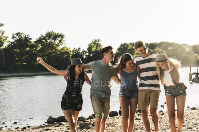 Группа счастливых друзей рука об руку на берегу реки — стоковое фото