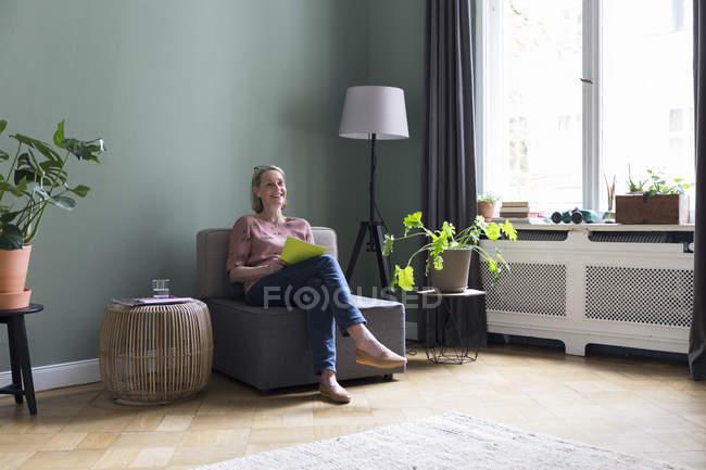 Mujer madura sonriente sentada en sillón en casa - foto de stock