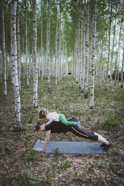 Mujer haciendo ejercicio con una niña pequeña en el bosque - foto de stock