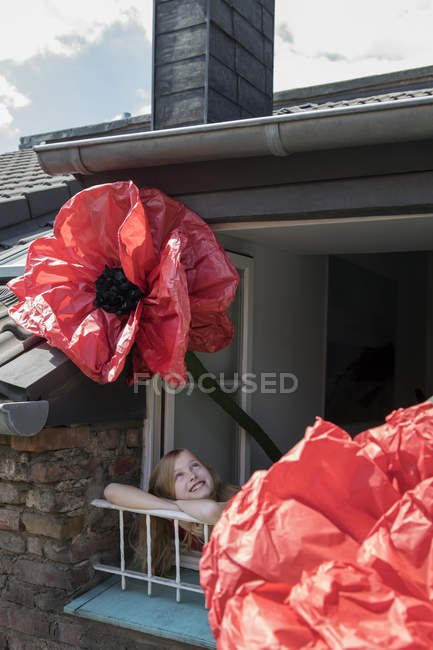 Happy girl with oversized redc artifical flower leaning out of window — Stock Photo