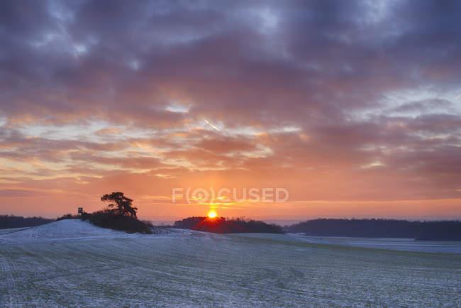 Alemanha, Baviera, Nascer do sol sobre a paisagem rural com campos e florestas no inverno — Fotografia de Stock