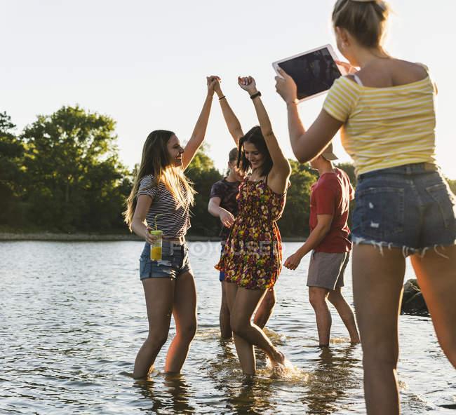 Группа счастливых друзей с табличкой в реке на закате — стоковое фото