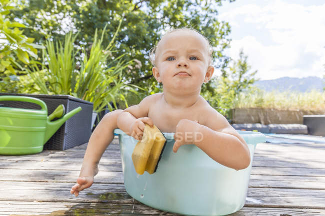 Boy sitting in baby bathtub — Stock Photo