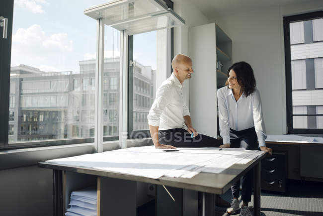 Two architects working in office, discussing blueprints on table — Stock Photo