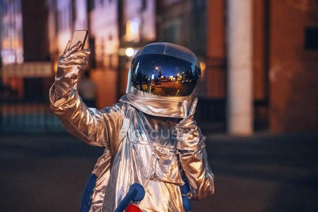 Spaceman en la ciudad por la noche tomando una selfie con smartphone - foto de stock