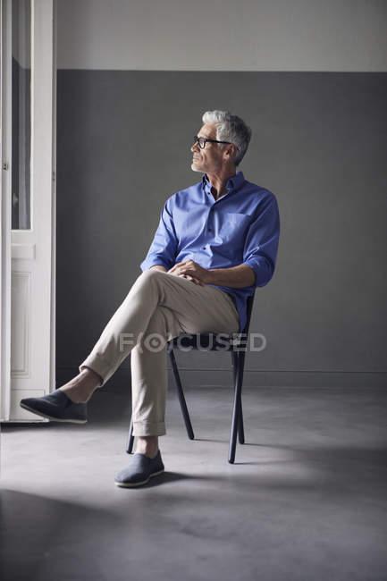 Пенсивна зріла людина сидить на стільці вдома і дивиться — стокове фото