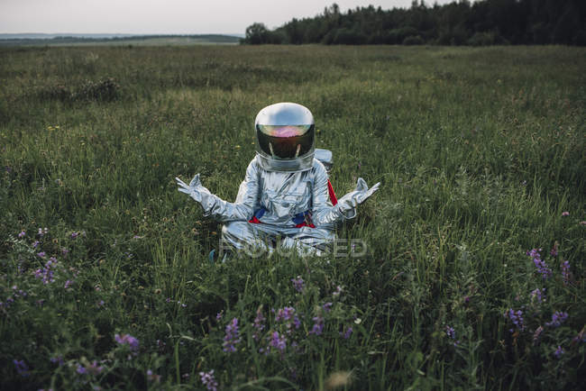 Spaceman exploring nature, sitting in meadow, meditating — Stock Photo