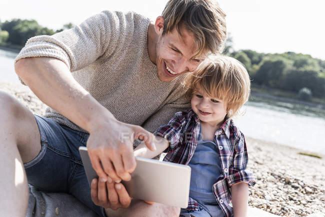 Vater und Sohn spielen am Flussufer auf digitalem Tablet — Stockfoto