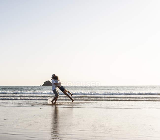 Junges Paar umarmt sich am Sandstrand — Stockfoto