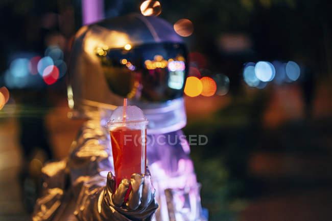 Spaceman en la ciudad por la noche sosteniendo una bebida para llevar - foto de stock