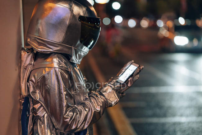 Spaceman on city street at night using cell phone — Stock Photo