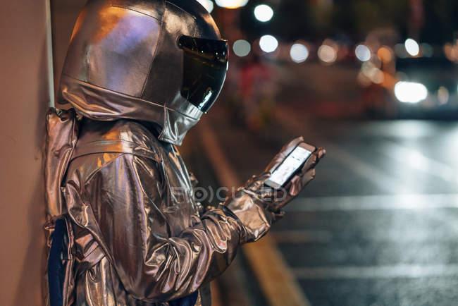 Spaceman en la calle de la ciudad por la noche usando el teléfono celular - foto de stock
