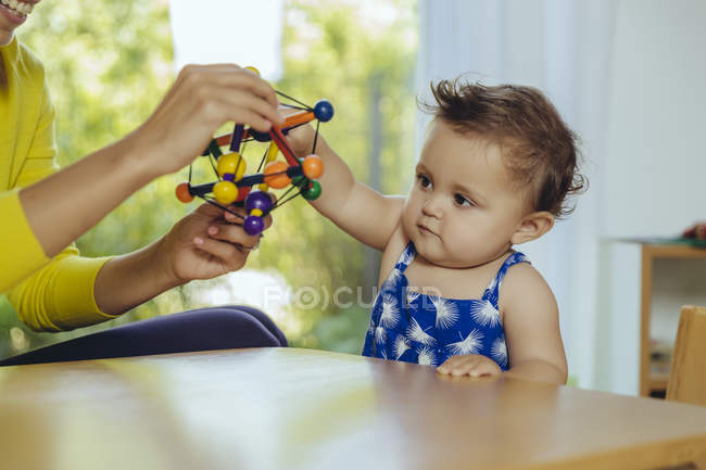 Mother and baby daughter playing at table at home — Stock Photo