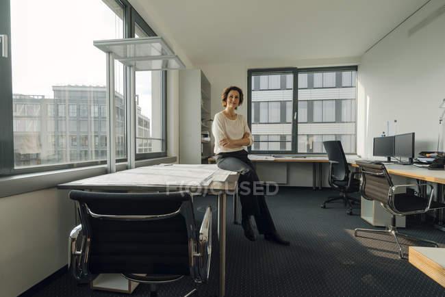 Успішна бізнесжінка сидить на столі в своєму кабінеті — стокове фото